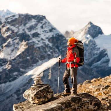 a mountain climber standing on a cliff enjoying sunlight